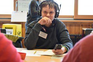"""Bild: ein junge mit Kopfhörern und wichtigem """"Chefredakteur"""" Schild"""