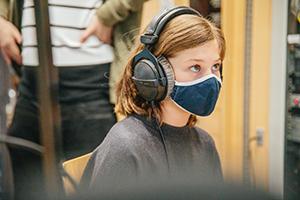Eine Teilnehmerin mit Maske schaut auf den Sendeplan im Studio